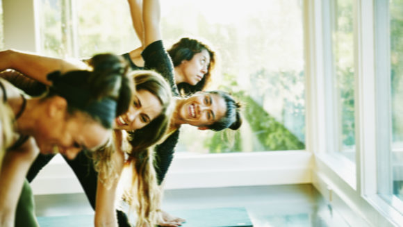 Woman laughing with friends during yoga class